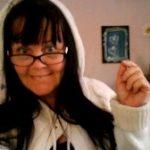 Anno Paananen i huvtröja och glasögon med mörka bågar. I sin vänstra hand håller hon upp ett blått kort med ett par ljusa hjärtan.