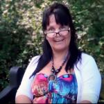 Anno Paananen läser ur boken ANNOlunda tankar om tankar.. Hon sitter på en bänk framför en häck med gröna blad. Hon har på sig en vit cardigan, under den är ett färgglatt plagg i turkost, blått och rosa. Hon ler med ögonen, bakom sina mörka glasögonbågar.