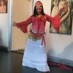 Anno Paananen dansar frigörande dansen Fritt Flöde. Hon har på sig en ceriserosa knytblus och en lång vit kjol som når ner till golvet. I håret och runt höfterna bär hon rosa band prydda med guldmynt. Anno är barfota.