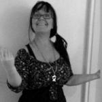 Svartvit bild. Anno Paananen, Zentrab, står och gestikulerar brett med händerna i sin roll som föreläsare. Hon tittar glatt och förtroendeingivande in i kameran.
