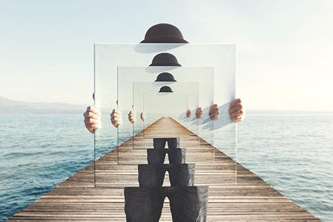 Person stående på en brygga med en canvas-tavla framför sig. Tavlan har ett speciellt djup och visar just den bilden med personen på bryggan, om och om igen.