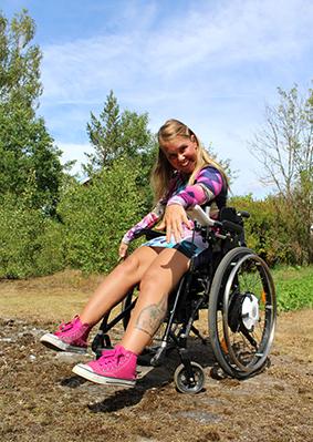 Moha Frikraft i rosa skor och färgglada kläder. Hon sitter i rullstol utomhus, träden har gröna löv och himlen är blå. Foto Bodil Mattsin