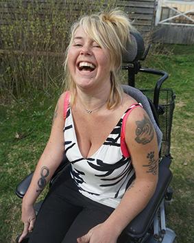 Föreläsaren Moha Frikraft skrattar. Hon har långt, uppsatt, blont hår. Hon har på sig ett vitt linne med svart mönster..