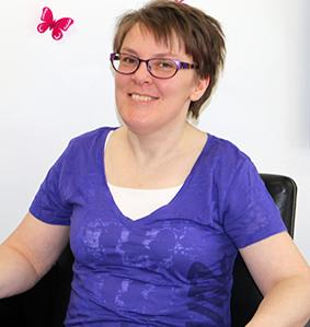 Föreläsaren Sara Edström ler mot kameran. Hon har kort, brunt hår och mörka glasögonbågar. Hon har på sig en kortärmad lilablå tröja och på den vita väggen i bakgrunden sitter en rosa fjäril.