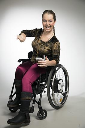Moha Frikraft sprudlande glad sittandes i sin rullstol. Hon har långt hår uppsatt i två flätor, guldfärgad tröja, plommonfärgade tajts och svarta skor med högt skaft.
